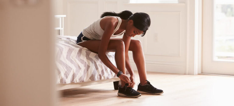 Young Woman Tying Athletic Shoes on Bed